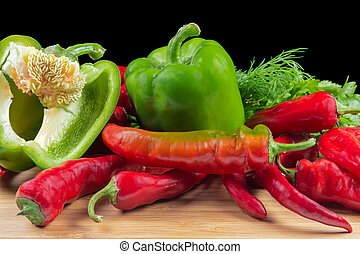 Whole and half of green bell pepper, chili on black background