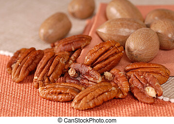 Several whole and shelled pecans on a table
