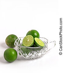 Whole and slice green limes in glass cup on white background.