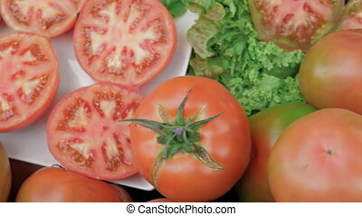 Whole and sliced tomatoes on lettuce - Ripe sliced and whole...