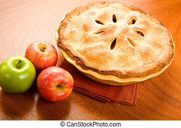 Whole apple pie in yellow baking dish on wood surface