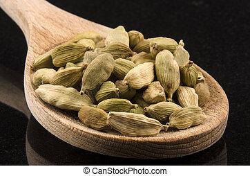 whole cardamom on a kitchen spoon