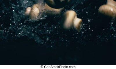 Whole champignon mushrooms splash on dark wet surface. Slow...