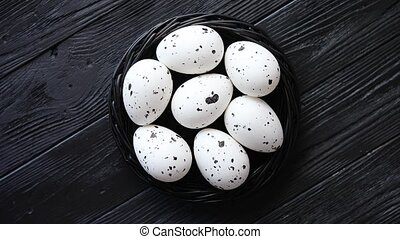 Whole Chicken eggs in a nest on a black rustic wooden...