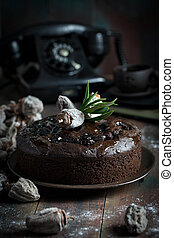 Whole chocolate cake on dark wooden table