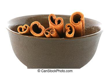 Whole cinnamon sticks in brown bowl