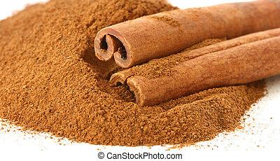 Whole cinnamon sticks on heap of ground cinnamon