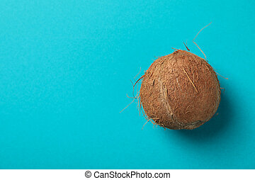 Whole coconut on blue background, top view