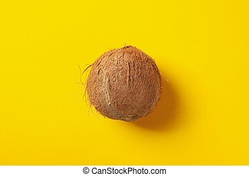 Whole coconut on yellow background, top view