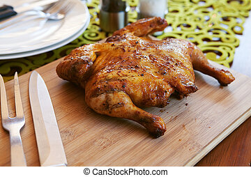 Whole cooked chicken with cutlery and spices