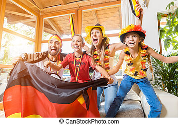Whole family cheering for the German soccer team in front of TV