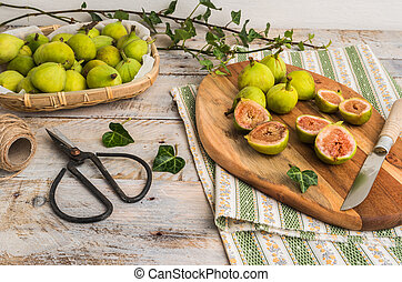 Whole figs and figs sliced in half on top of a rustic wooden table.