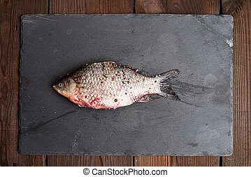 whole fresh crucian fish with scales lies on a black slate board