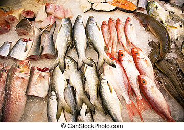 whole fresh fishes are offered in the fish market in asia