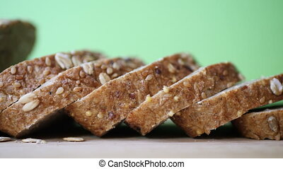 Whole grain bread on wooden table against green screen