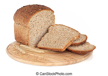 Whole grain loaf on a rustic carved wooden bread board with wheat ears isolated over white background.