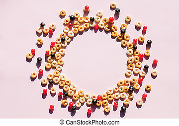 Whole grain cereal rings as circle on soft pink background. Healthy and Delicious breakfast. Top view. Copy space. circle of Breakfast cereal, corn flakes with berries.