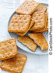 Whole grain crackers on a white plate.