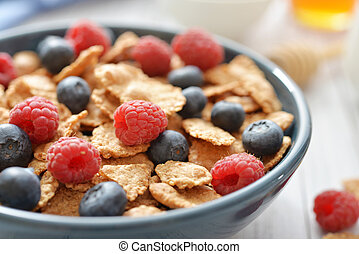 Whole-grain flakes in bowl with fresh berries on light...
