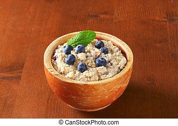 Bowl of whole grain oat porridge with blueberries