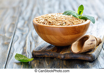 Whole grain oats in a bowl and wooden scoop.