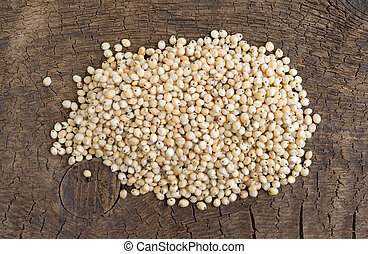 Whole grain sorghum seeds on an old board.