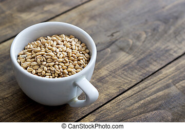 whole grain wheat in a cup over rustic wooden background