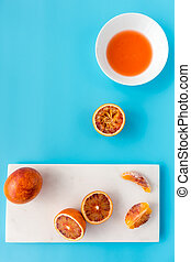 Whole, Halved and Squeezed Blood Oranges on Blue