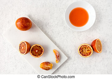 Whole, Halved and Squeezed Blood Oranges on White