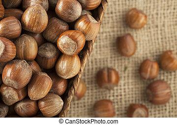 Close-up of whole unshelled hazelnuts in basket