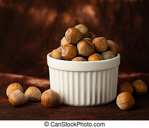 whole hazelnuts on a brown background