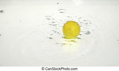 Whole lemon drops into the water. White background. Slow...