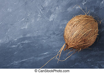 Whole natural coconuton isolated on gray blue concrete background. Top view, close-up. Copy space