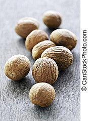 Whole nutmeg seeds on wooden table background