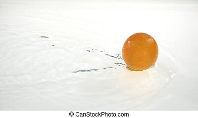 Whole orange rolls on the water. White background. Slow...