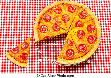 Whole pepperoni pizza on rack with slice removed. Red gingham tablecloth.