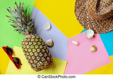 Whole pineapple on colorful background with hat, glasses, seashells, top view. Modern summer concept