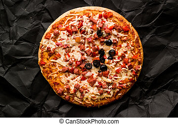 Whole pizza with ham, cheese and olive on a black surface.