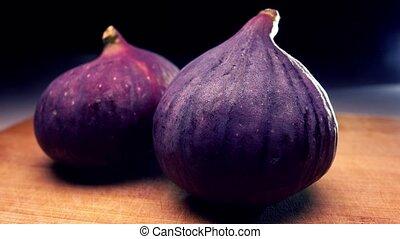 Whole ripe figs on cutting board. 4K close up pan shot -...