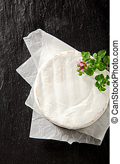 Whole ripened fresh round camembert cheese on a folded paper...
