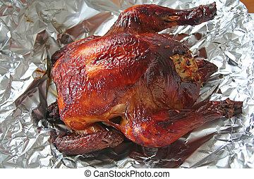Whole roast chicken wth rice stuffing in aluminum foil