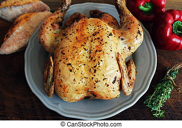 Whole roasted chicken on rustic table