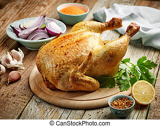 whole roasted chicken on wooden kitchen table