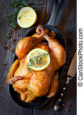 Whole roasted chicken with lemon and thyme on a pan. Rustic...