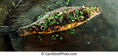 High Angle View of Whole Roasted Fish Garnished with Red and Green Onions on Rustic Wooden Cutting Board