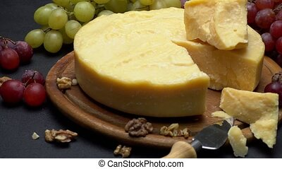 Whole round Head parmesan cheese, wine and grapeson wooden...