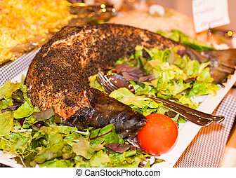 Whole salmon fish cooked in oven with green salad