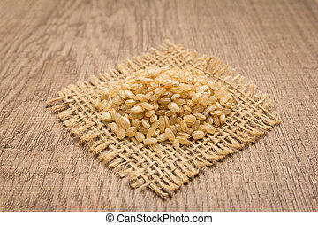 Whole Short Grain Rice Seed. Grains on square cutout of jute. Wooden table. Selective focus.