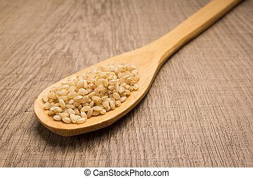 Whole Short Grain Rice Seed. Spoon and grains over wooden table.