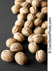 Whole walnuts on black background, side view. Close-up.